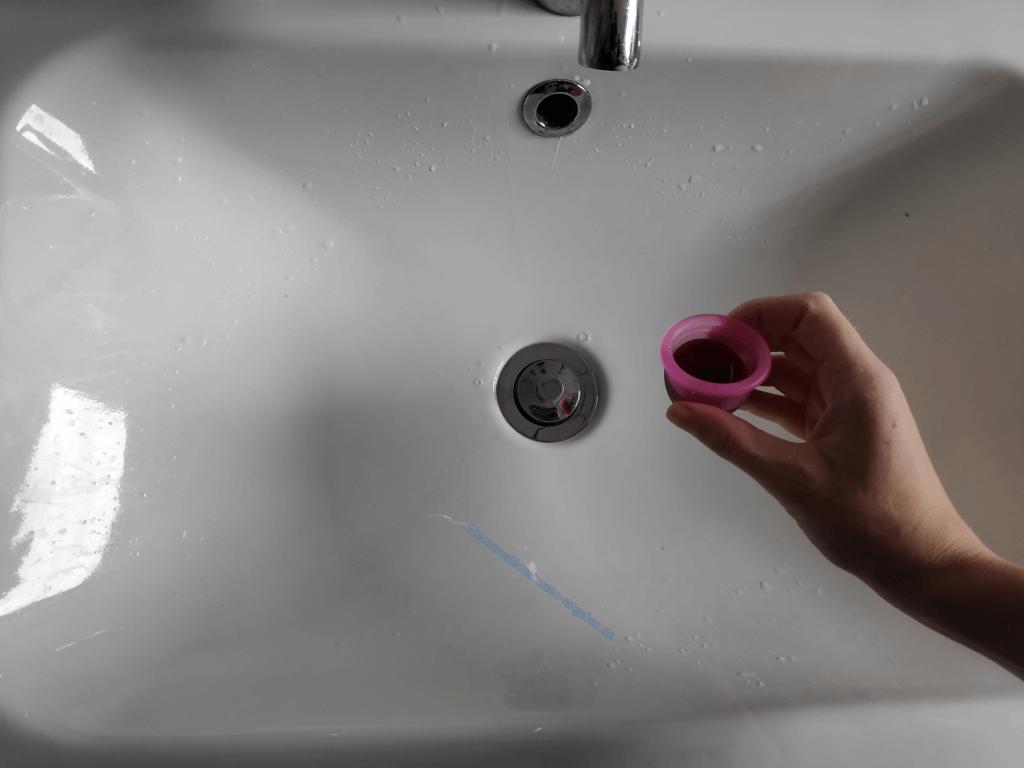 Menstruationstasse und Waschbecken